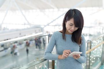 Woman using mobile phone at airport