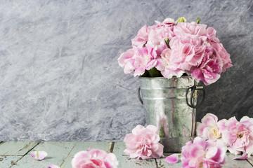 Pink carnation flowers in zinc bucket on old wood