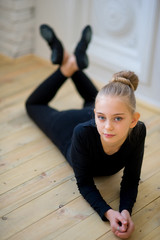 Young ballet dancer lying near the wall