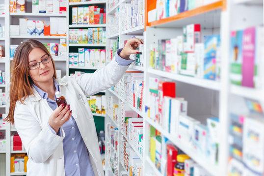 Woman pharmacist holding prescription checking medicine in pharmacy (or drugstore