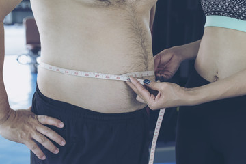 Trainer measuring obese man waist body fat. Before starting an e