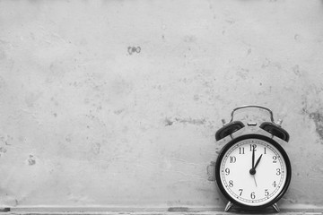 alarm clock showing one o'clock on wooden background. black and white