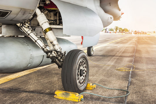 Detail part of wheel and brake system of f16 falcon fighter jet military aircraft on the ground in runway