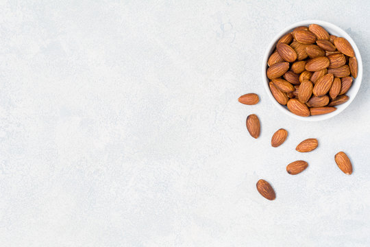 Almonds in bowl on bright background with copy space for text