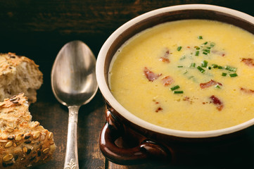 Corn cream soup with bacon (chowder) on wooden background.