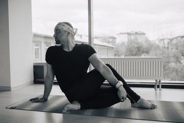 Experienced yoga man doing various poses indoors, panoramic city view at background