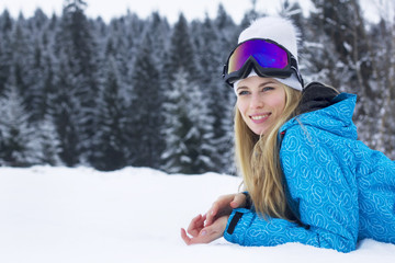 Smiling beautiful young woman with long blonde hair in snow jacket, white hat and goggles for skiing.