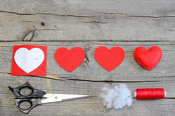 How to make stuffed felt heart for Valentine's day. Handmade red felt heart, cut felt pieces, paper template, scissors, thread on a wooden background. Simple and cheap Valentine's day crafts