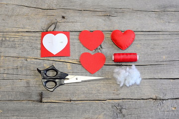 How to hand sew a felt heart for Valentine's day. Tutorial. Red felt heart, cut felt pieces in shape of a heart, synthetic filler, paper template, scissors, thread, needle on a wooden table. Top view