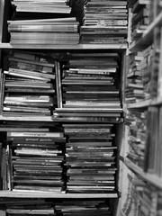 BLACK AND WHITE PHOTO OF BOOKS CRAMMED IN BOOKSHELF
