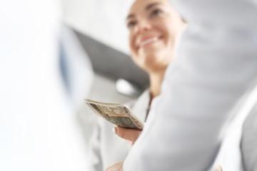 Pieniądze. Plik banknotów przekazywany z ręki do ręki.