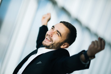 Happy Businessman executive raising fists in excitement in office Wall mural