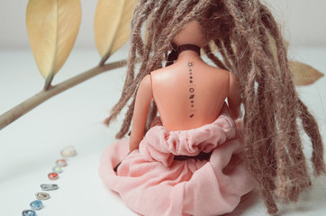 Doll with dreadlocks and tattoo with solar system
