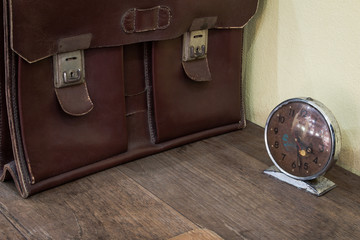 Brown antique schoolbag vintage and vintage clock on old wooden desk. School in the past concept.
