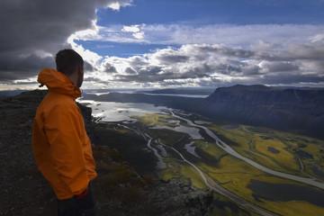 Male hiker enjoying the view over rapadalen river delta in rainy landscape