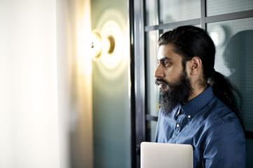 Asian businessman standing in an office doorway