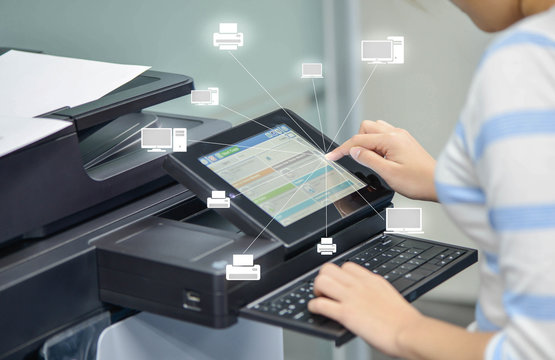 Business woman is using the printer to scanning document to netw