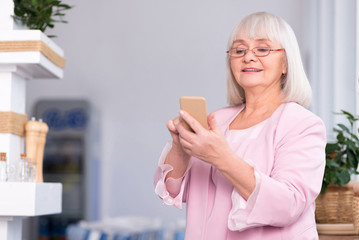 Excited senior woman using her phone