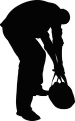 Silhouette of a man bending over and trying to lift a heavy bag.