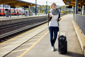 Woman With Luggage And Coffee Cup Waiting At Train Station