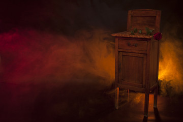 Bedside table in a dark burning room. Red rose on the table