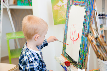a child draws a picture paints on art lesson