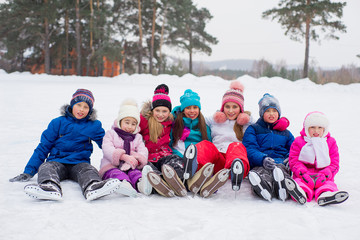 group of kids sitting on the ice