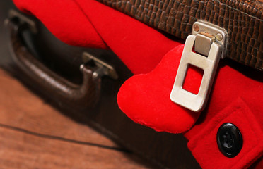 Clothes in old suitcase, red coat.