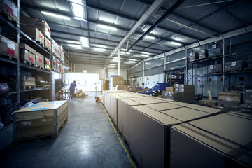 warehouse interior with paper boxes and worker with forklift in blue vintage color tone
