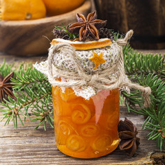 Homemade jam handmade orange peel in the form of snails in a small glass jar as  gift for the new year on  wooden background with fir branches and oranges in the . selective focus