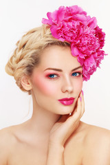 Portrait of young beautiful healthy blonde woman with clean make-up and pink peony flowers in her hair touching her face