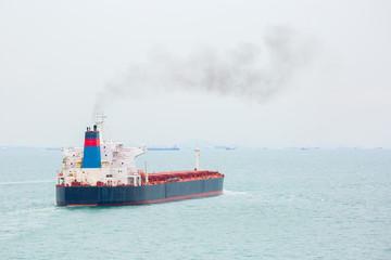 Smoking cargo ship is underway.