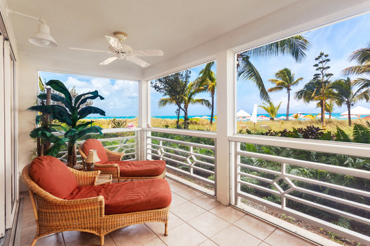 Comfortable chaises in a large screened porch overlook the dunes and Grace Bay Beach, Turks and Caicos