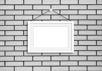 Blank frame hanging on cords  against white bricks wall, exhibition style decor mock up