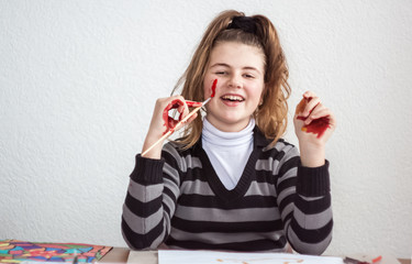 Girl painting with brush and colorful paint and smeared hands of