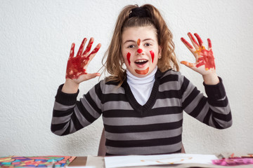 Girl painting with brush and colorful paint with smeared face an