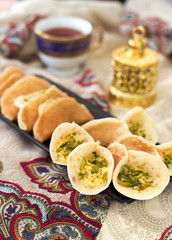 Traditional Arabic qataif crepes stuffed with cream and pistachios, prepared for iftar in Ramadan on paisley background above