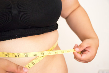 Woman body fat with measure tape.