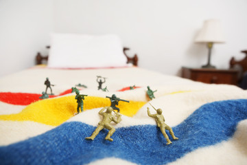 Toy soldiers on a bed