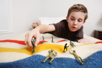 Young boy laying on his bed playing with toy soldiers
