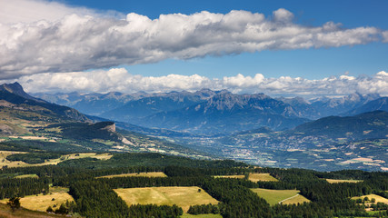 """Panoramic elevated view on Bayard plateau with view of Chapeau de Napoleon and Grand Morgon in the distance. In the center, the city of """"La Batie Neuve"""". Summer in the Hautes Alpes, Alps, France"""