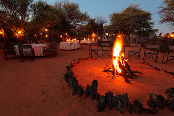 Nighttime campfire and decorated tables for outdoor safari catering .
