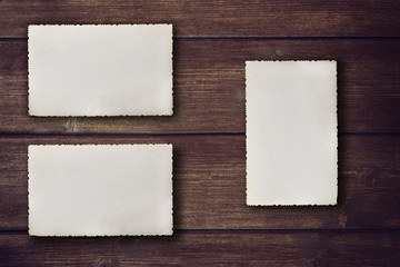 Blank vintage photos with jagged edges are lying on the brown wooden desk. Two horizontally and one vertically are ready for your text.