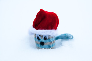 Knitted toy in a red cap in the snow.