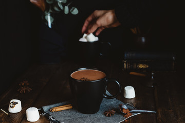 Food Scene Featuring Mug of Hot Chocolate on Rustic Table with Woman Choosing Marshmallow Toppings in Background
