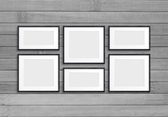 Collage of black wooden frames on old wood panels wall. Retro style mock up