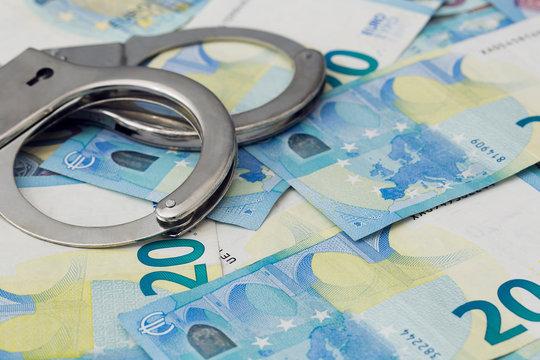 Handschellen liegen auf Geldscheinen