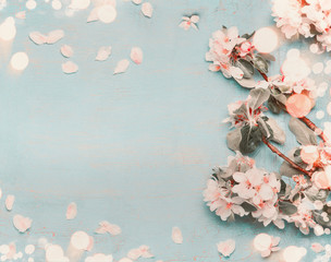 Pretty spring blossom on light blue background with bokeh, top view, pastel color, border