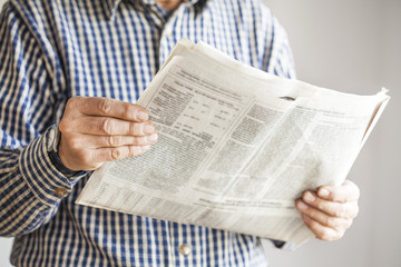 Man reading newspaper on gray background
