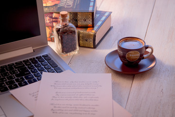 Laptop, books, cup of coffee and poems on the old wooden table. Shakespeare Poems